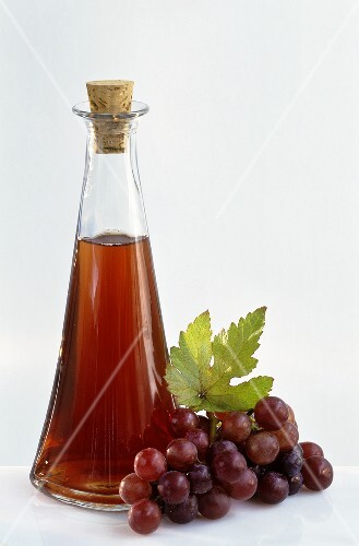 A bottle of grape vinegar with fresh grapes