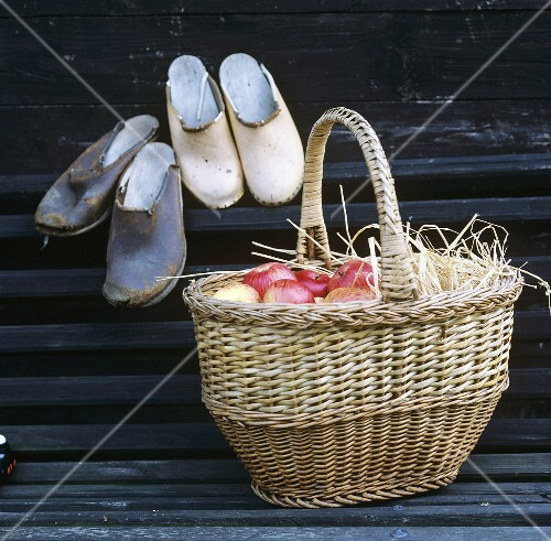 Basket of apples on bench, two pairs of garden shoes behind