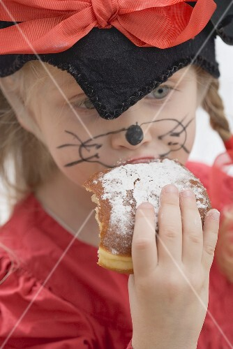Girl in fancy dress biting into a doughnut (Carnival)