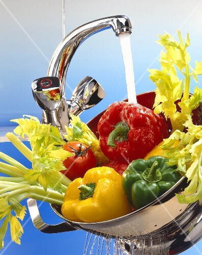 Washing vegetables under running water