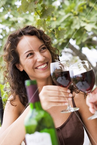 Young woman clinking glass of red wine