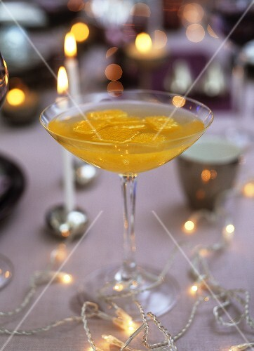 Sparkling wine & peach cocktail with orange juice ice cubes