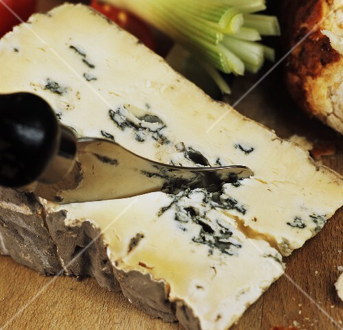 A piece of blue cheese with cheese knife