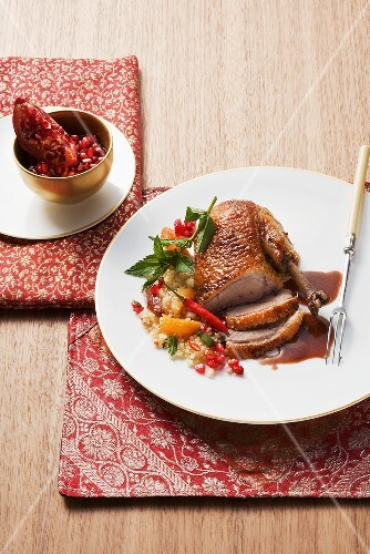 Roast duck with fruits and chilli on a bed of couscous