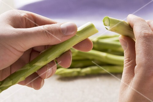 The woody end being broken off green asparagus