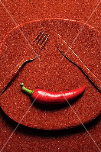 Plate covered in chilli powder with knife, fork & chilli (a face)