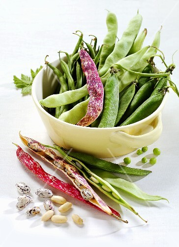 Various types of beans and peas in and beside a pot