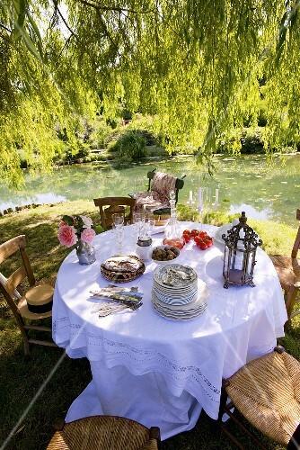 gedeckter tisch am teich im romantischen garten bild kaufen 366810 stockfood. Black Bedroom Furniture Sets. Home Design Ideas