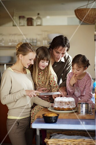Young family cutting a cake