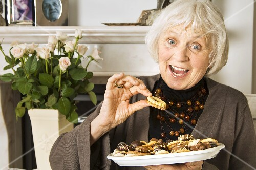 Elderly lady eating biscuits