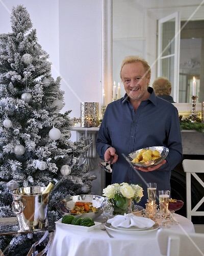 A man serving roast potatoes for Christmas dinner