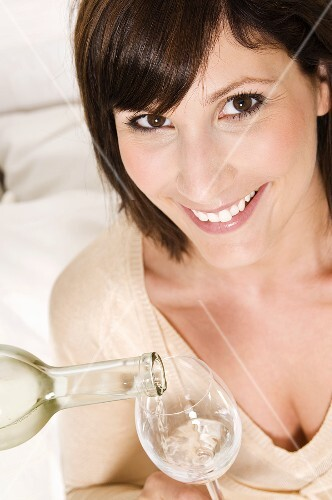 Woman having a glass of white wine poured