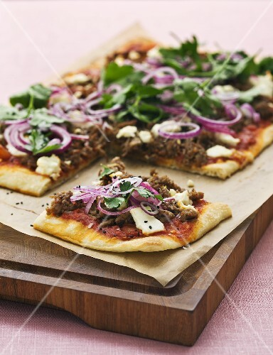 Pizza topped with mince, cheese, onions and sesame seeds