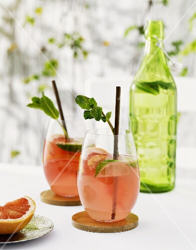 Pink grapefruit drinks with lime wedges and mint