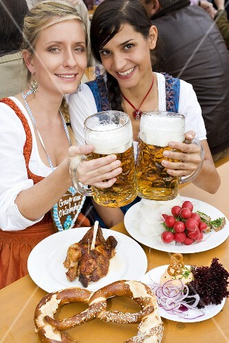 Two women with typical snacks clinking tankards of beer (Oktoberfest)