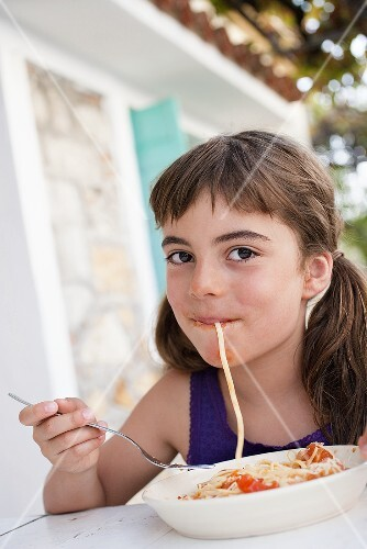 Girl with spaghetti in her mouth