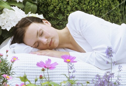 Young woman asleep in garden