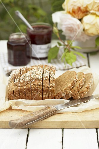 Irish wholemeal bread on chopping board, jam, roses
