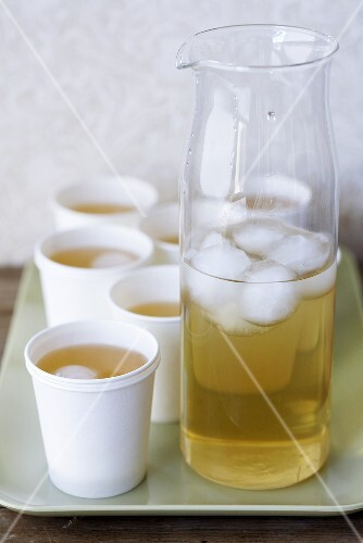 Elderflower liqueur with ice in carafe and paper cups