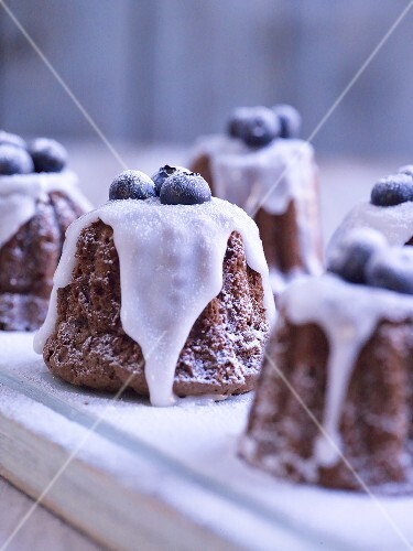Mini chocolate cakes with icing sugar and blue berries