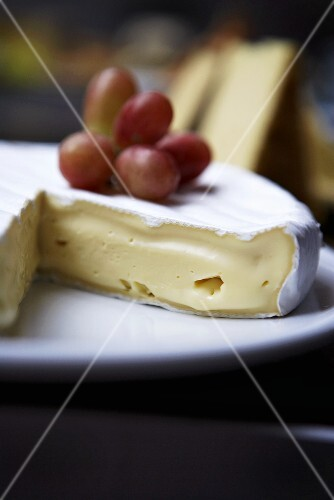 Brie, a section removed, with grapes