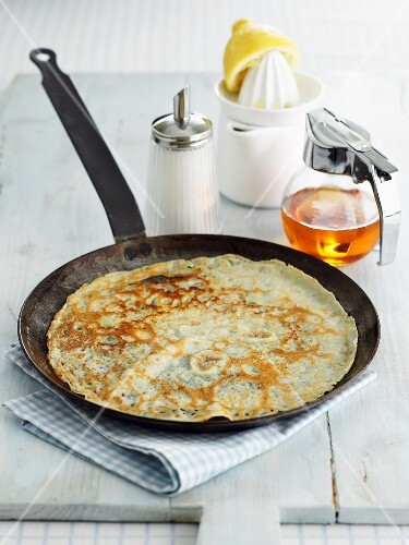 Crêpe in frying pan, maple syrup, sugar, lemon juice