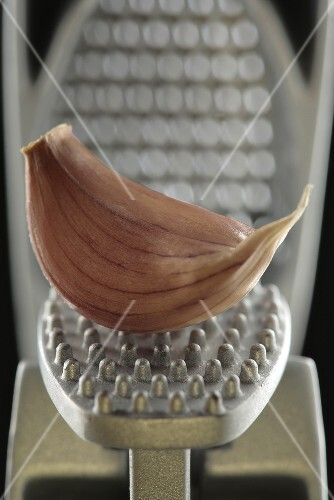 A garlic clove in a garlic press (close-up)