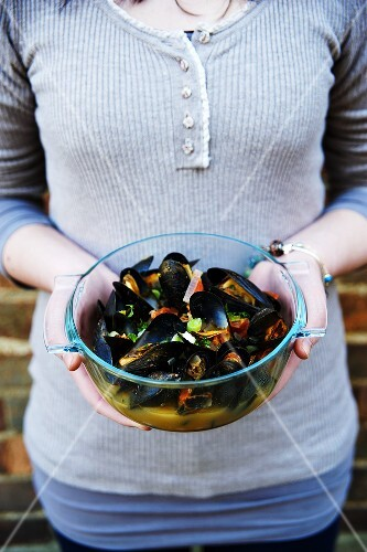 A woman holding a bowl of mussels