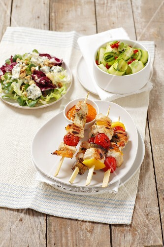 Grilled kebabs with chicken and vegetables and salads