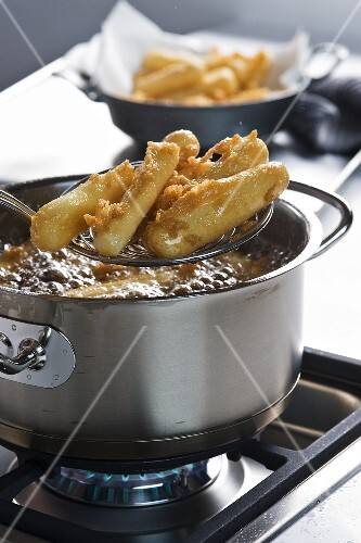Battered black salsify being fried in hot oil