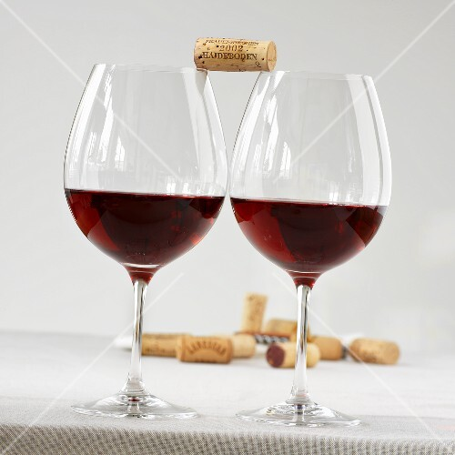 Two glasses of red wine with a cork balanced between them