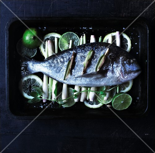 Raw bream on lemongrass and lime slices