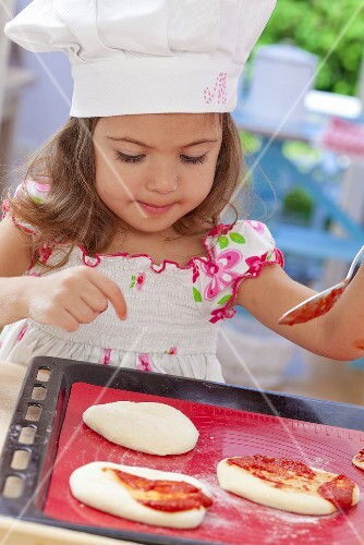 A little girl spreading tomato sauce onto pizza dough