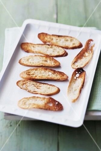 Grilled baguette slices on a baking sheet