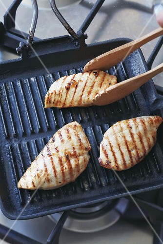 Grilling chicken breast on a grill pan