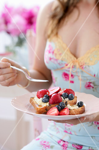 A woman eating a bread dessert with fresh berries