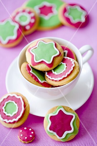 Assorted colorfully decorated Christmas cookies in and next to a teacup