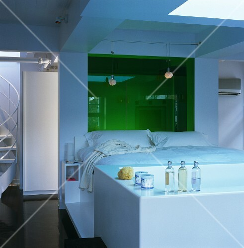 The white platform bed in this open-plan bedroom has a bath positioned at the end of it and wardrobes behind the green glass panel