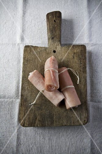 Detail of three strips of pork rind tied with string on a wooden chopping board