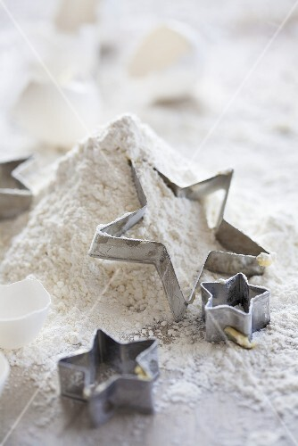 Star-shaped cutters on top of a pile of flour