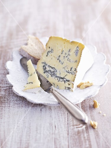 A slice of blue cheese on a plate with a knife