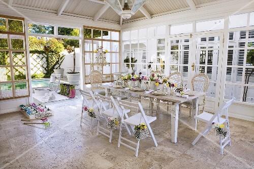 festlich gedeckter tisch mit blumenschmuck in einem wintergarten bild kaufen 456126 stockfood. Black Bedroom Furniture Sets. Home Design Ideas