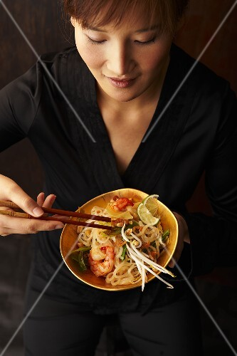 A woman eating pad thai (fried rice noodles, Thailand)