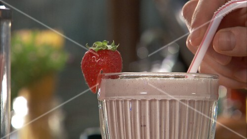 Pouring strawberry shake into glass and garnishing with strawberry