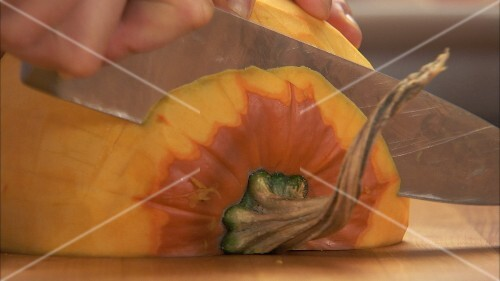 Slicing a peeled pumpkin half