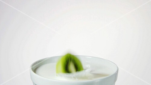 A slice of kiwi fruit falling into milk