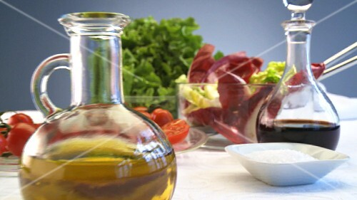 Salad, oil and vinegar on table