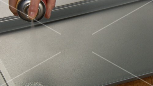 Spraying a baking tray with cooking spray