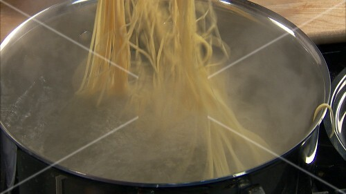Putting salt and spaghetti into boiling water