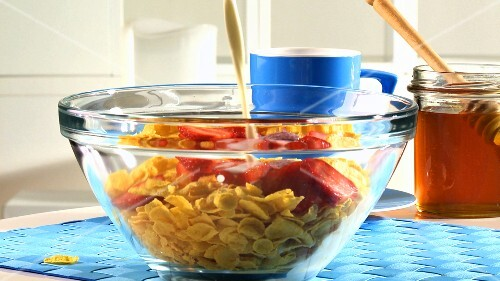 Cornflakes, Erdbeeren und Milch in eine Schale geben